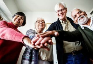 4 older people leaning in together