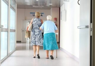 Older person walking down hospital corridor with help