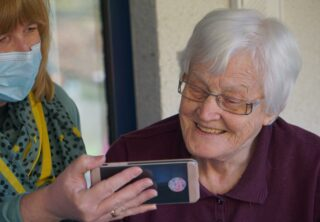 Older woman looking at something on a smart phone being held by a care worker